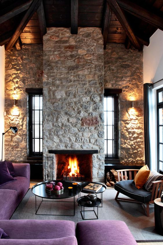 a bright contemporary living room with rough stone walls and a fireplace, purple furniture and elegant round tables