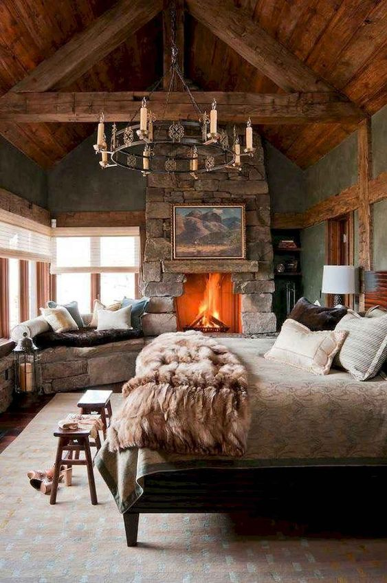 a cabin bedroom with a rough stone fireplace and a bench, a catchy chandelier, wooden items and a cozy linens