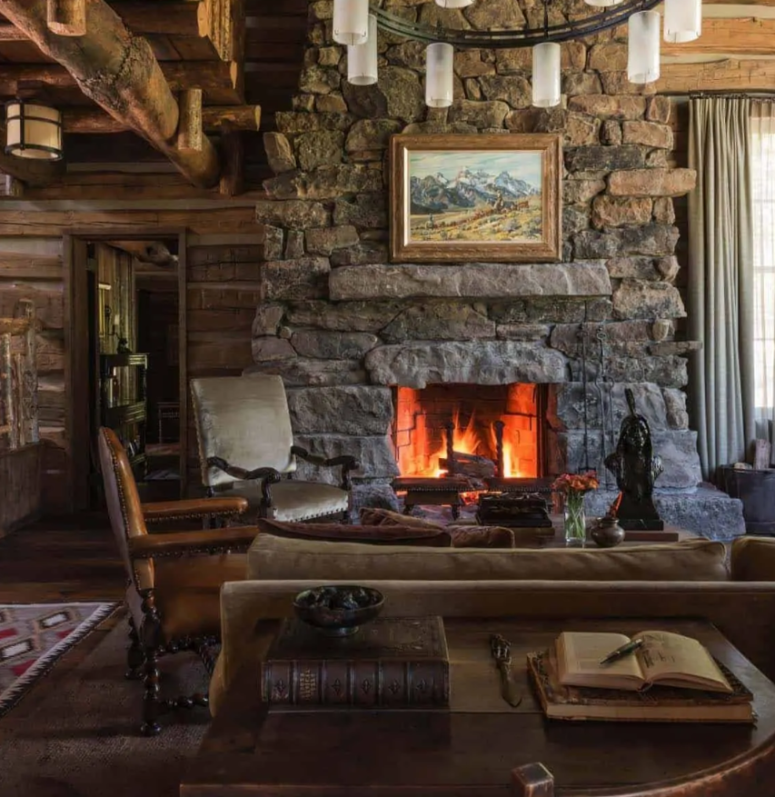 a cabin style living room done with lots of rough wood, a large stone hearth and vintage furniture of wood and leather
