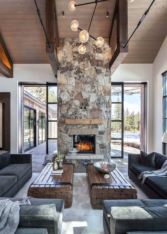 a chic contemporary cabin space with dark furniture, wood slab tables and a spectacular stone fireplace with a wooden mantel