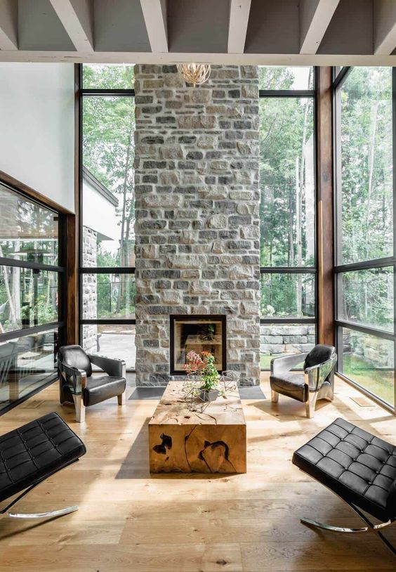 a chic contemporary living room with a stone fireplace as a centerpiece, black leather chairs and a wood slab table
