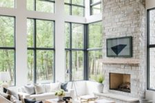 a clean and modern double-height living room with a grey stone fireplace and a wooden mantel as a centerpiece