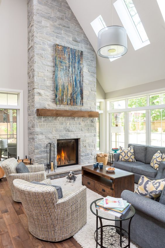 a clean double-height neutral living room with a grey stone fireplace with a wooden mantel and a bright blue artwork