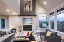 a clean modern living room in light shades and a built-in fireplace clad with white faux stone to match