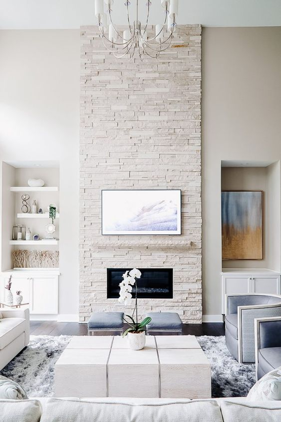a clean neutral living room with a white faux stone fireplace and some pastel blue touches here and there