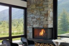 a contemporary cabin living room with a stone clad fireplace and firewood storage, chic furniture and lots of windows