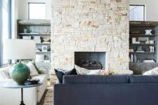 a contemporary living room in neutrals, with a double-height ceiling, a stone fireplace that warms up the space