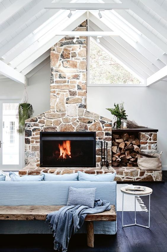 a contemporary living room with blue furniture, a stone hearth with a built-in modern fireplace and skylights