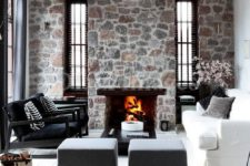 a contemporary monochromatic space with bright stone walls and a fireplace, elegant and laconic black and white furniture
