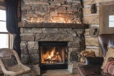 a dak cabin living room with a stone fireplace, antlers on the mantel, layered rugs and wicker and leather furniture