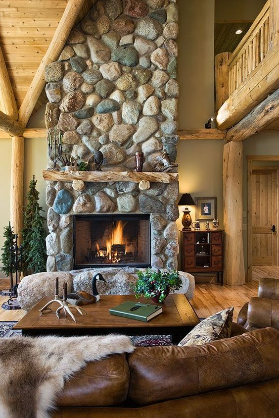 a gorgeous cabin space with a large scale stone fireplace with rocks at its base, leather and wood furniture