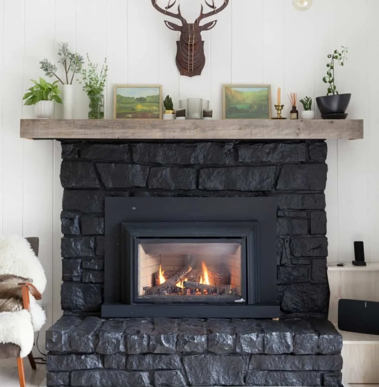 a large black stone clad fireplace with a wooden mantel is a great cabin or woodland touch to the space