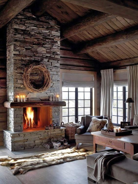 a moody neutral living room with a grey stone fireplace, vintage furniture, faux fur rugs and blankets and candles