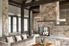 a neutral contemproary cabin living room with a stone double-sided fireplace, neutral furniture, wooden beams