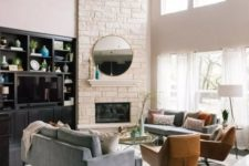 a stylish modern living room with a white faux stone corner fireplace with a small mantel, a round mirror and double-height windows