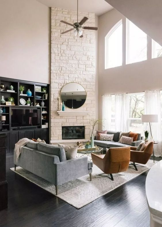 a stylish modern living room with a white faux stone corner fireplace with a small mantel, a round mirror and double height windows