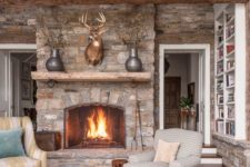 a welcoming cabin living room with stone walls and a fireplace, wooden beams, a jute rug and vintage furniture