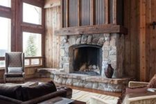 an elegant and chic cabin living room with rich stained woods, a stone and metal fireplace and vintage furniture