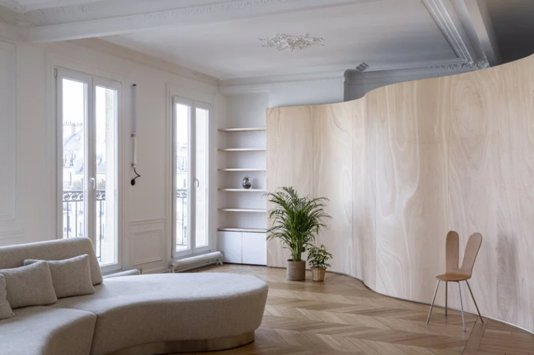 This typical Hausmann apartment in Paris got a renovation and redesign with a curved wooden space divider that doubles as an artwork