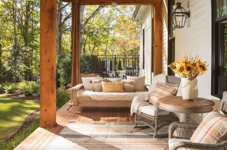 The front porch is very cozy, with wooden and wicker furniture and cozy textiles