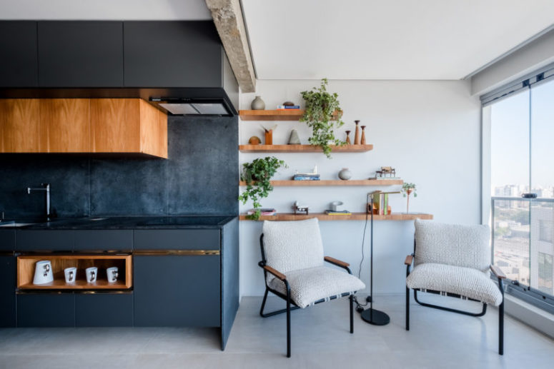 The kitchen is done in black, with matte surfaces, rich colored wooden touches and gold shiny ones