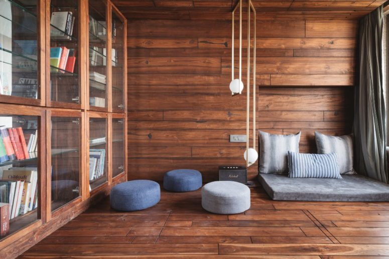 This stylish and cozy reading nook is clad with rich stained wood, contemproary furniture and lots of bookcases