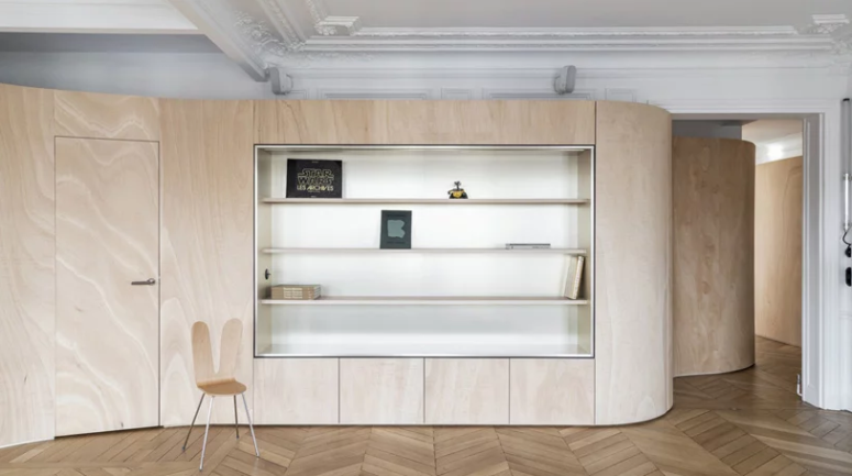 This wooden wall features some storage space, too, and it wraps the whole apartment dividing it into zones and keeping the historical touches seen