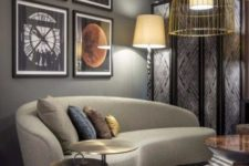 02 a catchy living room with a retro feel and a curved taupe sofa, a bold gallery wall and gold wire pendant lamps