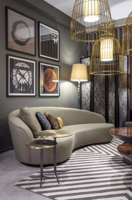 a catchy living room with a retro feel and a curved taupe sofa, a bold gallery wall and gold wire pendant lamps