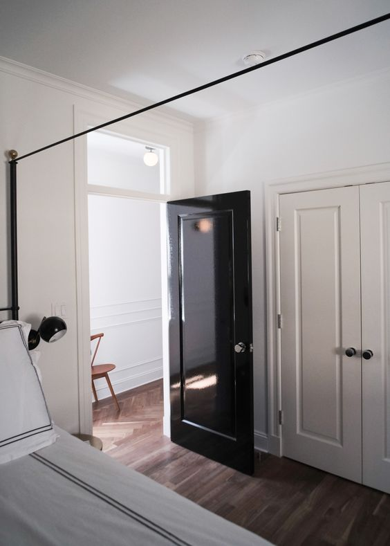 a glossy black door adds interest and chic to the neutral spaces and gives them a trendy feel