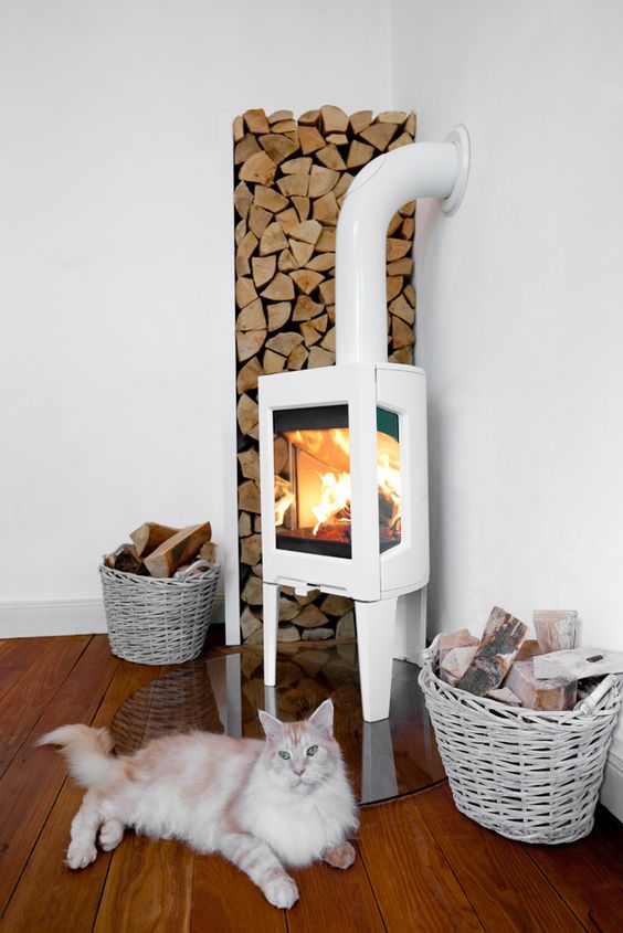 a modern white wood burning stove on a glass stand, with firewood in the corner and baskets for firewood