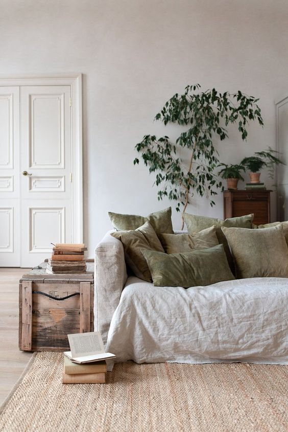 a neutral living room in various soft shades with plenty of texture and potted greenery and a tree