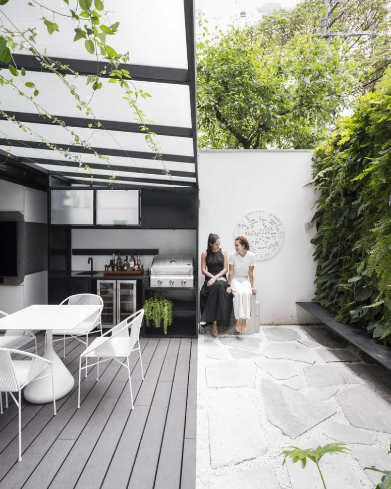 The kitchen opens up to a private courtyard with a green wall that enlivens the whole space at once