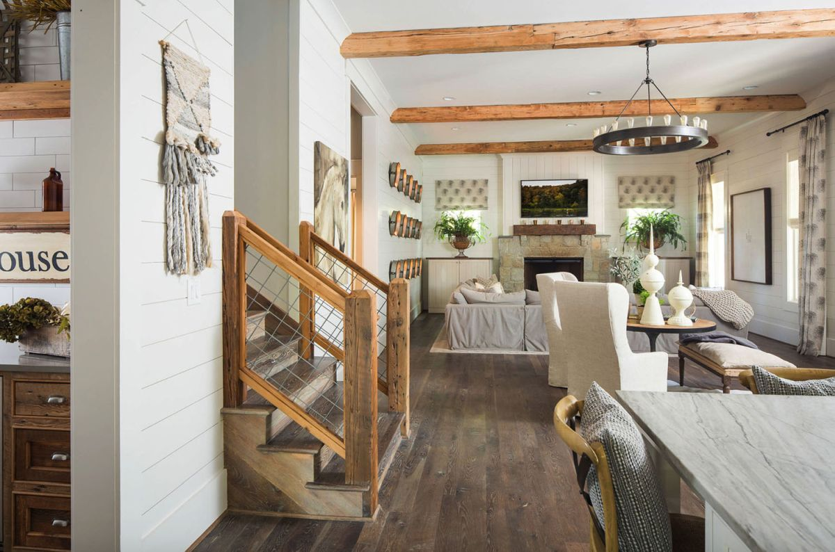 The open living space features all neutrals, a dark floor and wooden beams on the ceiling plus a matching staircase