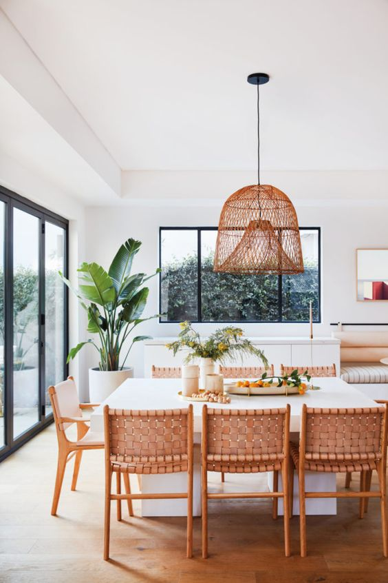 a Californian kitchen with a woven lamp, woven leather chairs and a large scale plant