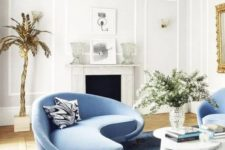 03 a charming living room with a curved blue sofa and matching chairs and a bold table that catch an eye