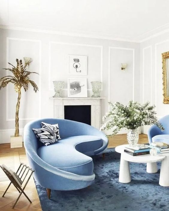a charming living room with a curved blue sofa and matching chairs and a bold table that catch an eye