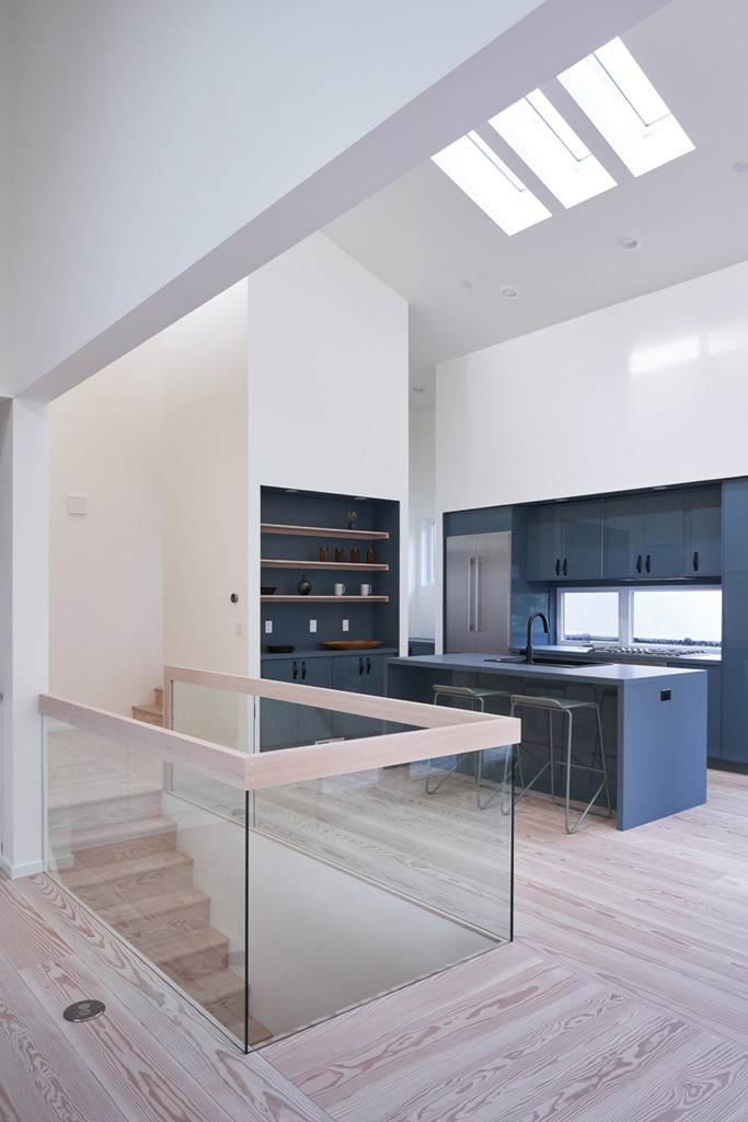 The kitchen is done minimal, with grey cabinets, with built-in shelves and a glass railing