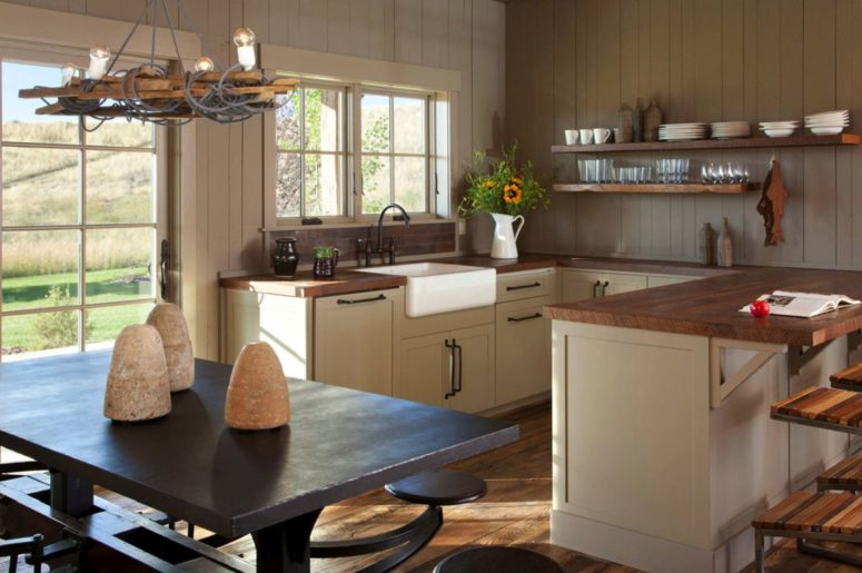 The kitchen is done with white wooden cabinets with wood countertops, there's an eating space with dark furniture