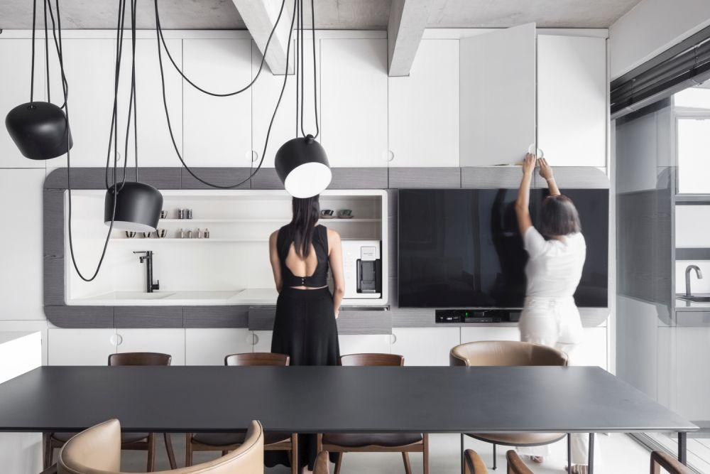 The kitchen itself is done with sleek white cabinets, with matte lamps and faucets plus a black table