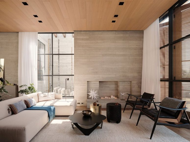 The living room is done with wood and plywood, in a neutral color palette and with catchy furniture pieces