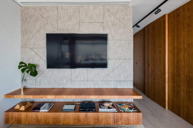 The storage is hidden behind rich-colored sliding doors, there's a TV and a sleek TV unit attached to the wall