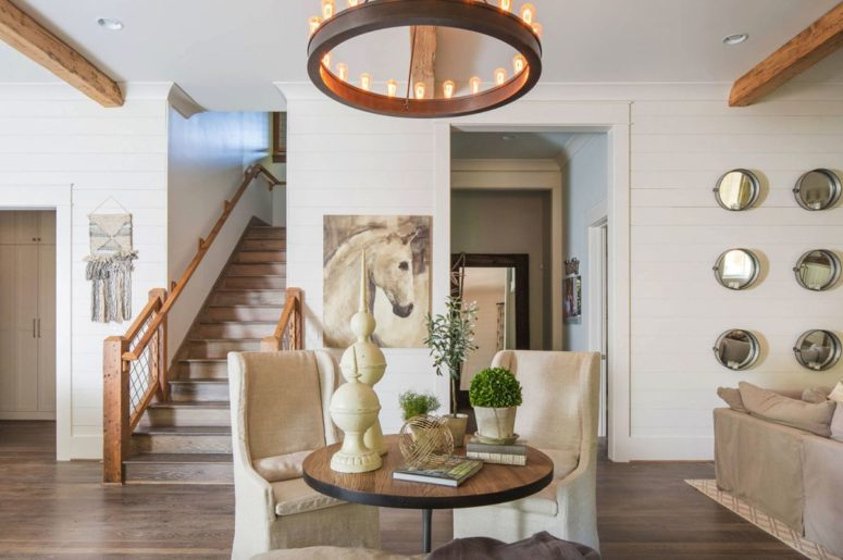 This cute sitting zone shows off two vintage chairs and is highlighted with a bold rustic chandelier, which is modern