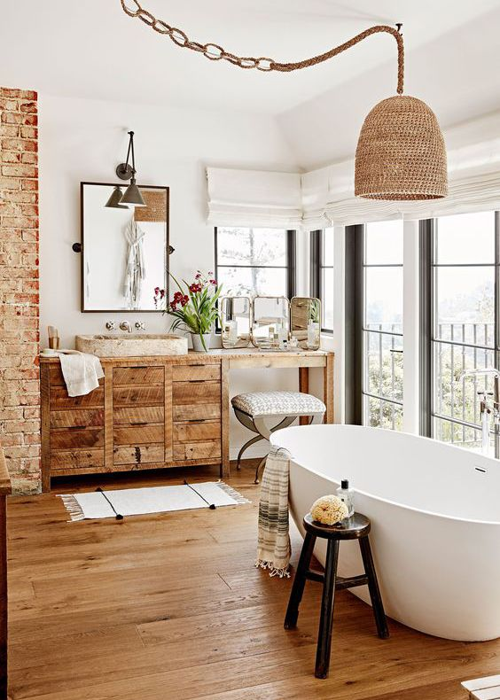 a Californian bathroom with a woven lampshade on a rope, a woodenvanity and a wooden floor