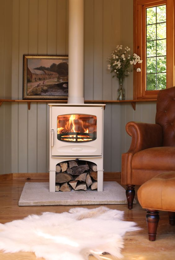 a white wood burning stove is an elegant idea, firewood under it is a cool idea to store it