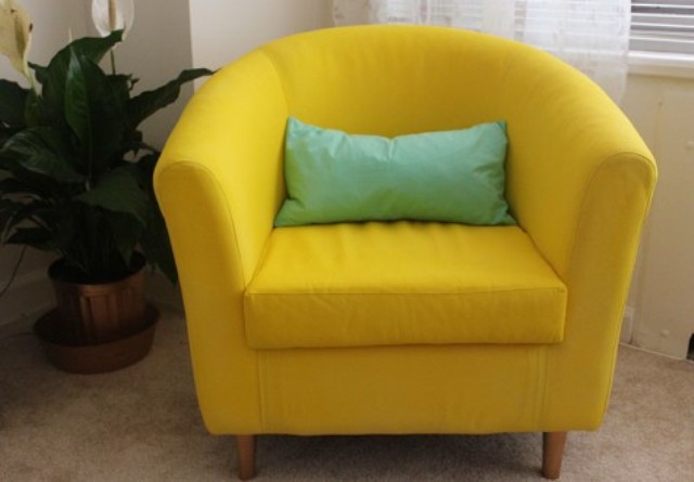 an IKEA Tullsta chair painted in bold yellow using fabric paint and with a mint pillow for a brighter look