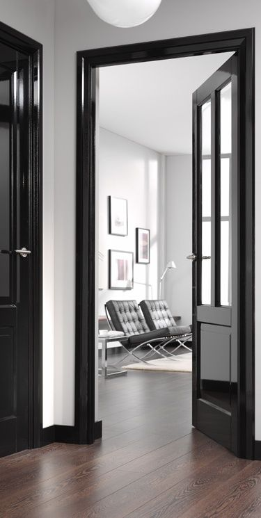 glossy black doors add catchiness and a slight shine to the neutral and monochromatic spaces like these ones