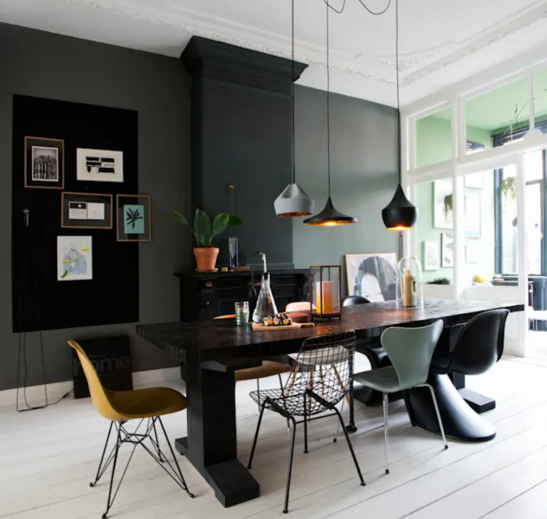 A large dining space is done with a black fireplace, a gallery wall, mismatching chairs, a black wooden table and pendant lamps