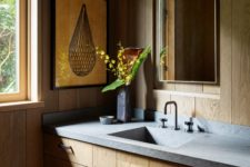 05 The bathroom is done with sleek plywood cabinets, a stone countertop and everything is clad with wood