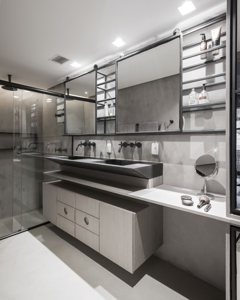 The bathroom is sleek and elegant, with plywood, concrete and stone, with a glass enclosed shower space